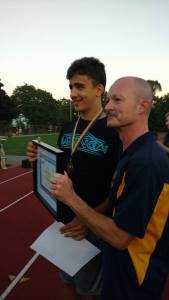 Coach Rob hands Mert his award.